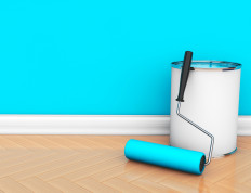 Painting of walls in a blue color. Paint can with roller brush
